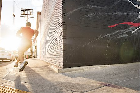 runner (male) - Rear view of male runner running on sidewalk Stock Photo - Premium Royalty-Free, Code: 614-08126723