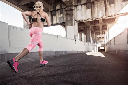 Female runner running under city bridge Stock Photo - Premium Royalty-Free, Code: 614-08126744