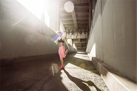 Female runner warming up under city bridge Stock Photo - Premium Royalty-Free, Code: 614-08126741