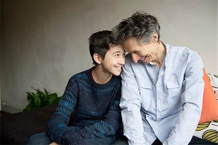 sweater - Teenage boy and father face to face on sofa Stock Photo - Premium Royalty-Free, Code: 614-08126750