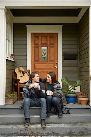front - Young couple sitting on porch step chatting Stock Photo - Premium Royalty-Free, Code: 614-08126760