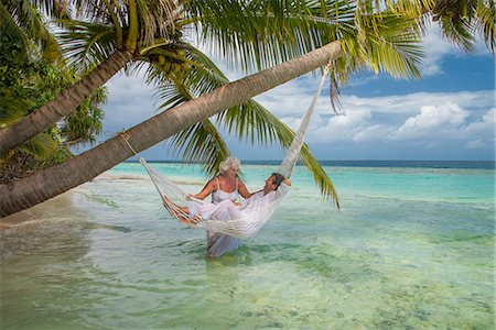 Senior man relaxing in hammock with woman, Maldives Stock Photo - Premium Royalty-Free, Code: 614-08126825
