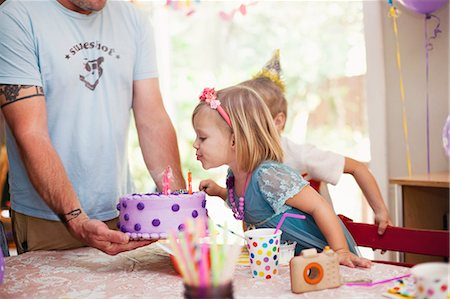 Portrait of blonde girl blowing out candles on purple cake Stock Photo - Premium Royalty-Free, Code: 614-08120070
