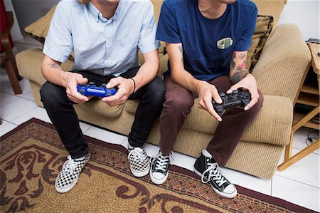 Two young men sitting on sofa, playing video game, low section Stock Photo - Premium Royalty-Free, Code: 614-08148645