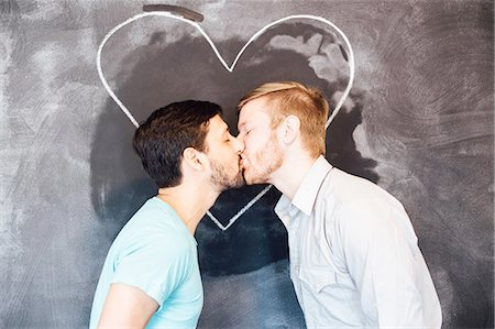 Male couple kissing in front of blackboard with chalk heart Stock Photo - Premium Royalty-Free, Code: 614-08148661