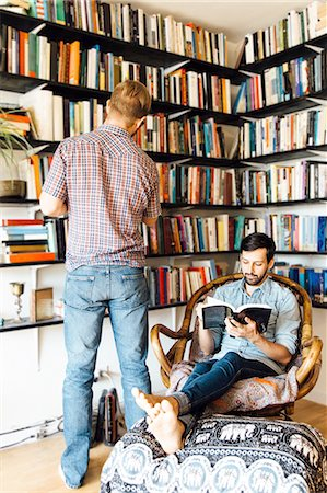 Male couple at home, reading and looking at books on bookshelf Stock Photo - Premium Royalty-Free, Code: 614-08148663