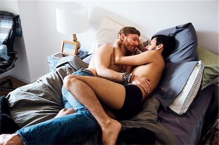 Male couple, partially dressed, lying on bed, embracing Stock Photo - Premium Royalty-Free, Code: 614-08148671