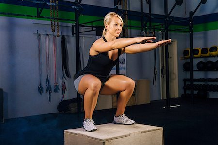 Young woman squatting on gym box with arms reaching out Stock Photo - Premium Royalty-Free, Code: 614-08202048