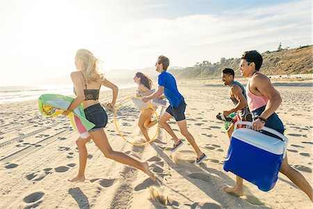 Group of friends running on beach, rear view Stock Photo - Premium Royalty-Free, Code: 614-08202252