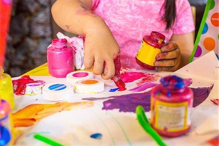 finger painting - Girl sitting at table, making art, using paint, focus on artwork Stock Photo - Premium Royalty-Free, Code: 614-08219827