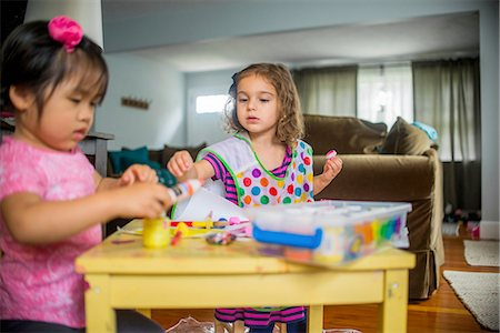 finger painting - Two young girls sitting at table, making art, using paint Stock Photo - Premium Royalty-Free, Code: 614-08219822