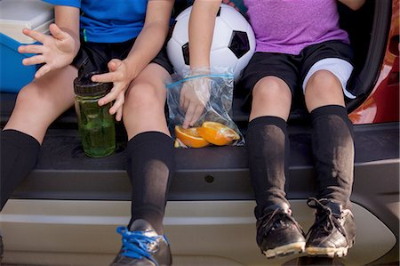 Waist down of boy and younger sister sitting in car boot eating oranges on football practice break Stock Photo - Premium Royalty-Free, Code: 614-08219838