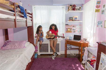 Girls sitting on bedroom windowsill singing and playing guitar Stock Photo - Premium Royalty-Free, Code: 614-08219930