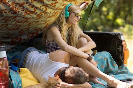 Young woman wearing headphones with boyfriend in pick up boot whilst camping Stock Photo - Premium Royalty-Free, Code: 614-08220143