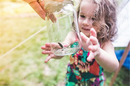 discovery - Grandfathers hand holding insect in jar for granddaughter Stock Photo - Premium Royalty-Free, Code: 614-08270014