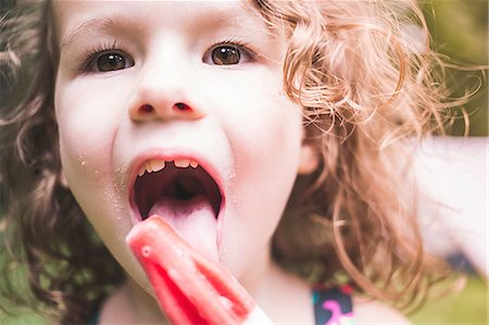 Close up of girl licking ice lolly Stock Photo - Premium Royalty-Free, Code: 614-08270022