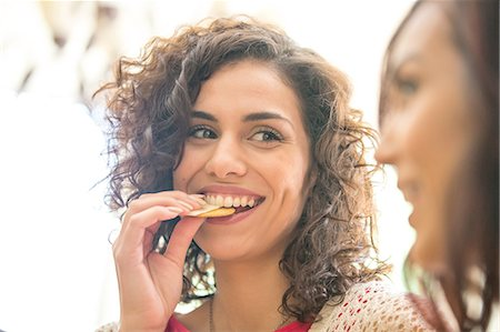 Young woman and sister snacking on cheese and biscuits Stock Photo - Premium Royalty-Free, Code: 614-08270121