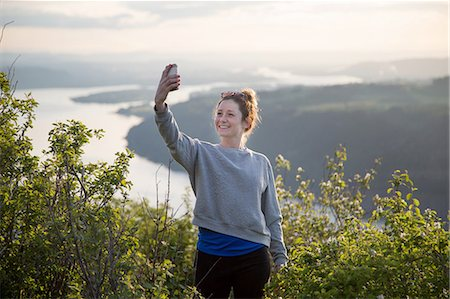 Woman taking selfie on hill, Angel's Rest, Columbia River Gorge, Oregon, USA Stock Photo - Premium Royalty-Free, Code: 614-08270143