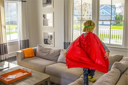 Boy with red cape playing on sofa Stock Photo - Premium Royalty-Free, Code: 614-08270157