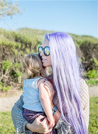 Young woman with long purple hair,  holding baby daughter Stock Photo - Premium Royalty-Free, Code: 614-08270177