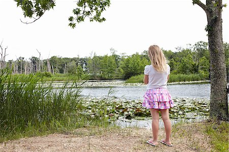 Rear of girl looking out over rural lake Stock Photo - Premium Royalty-Free, Code: 614-08270205