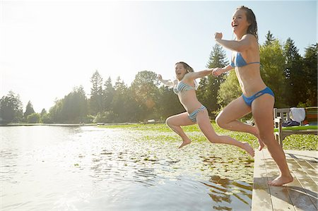 Girls in bikini jumping into lake, Seattle, Washington, USA Stock Photo - Premium Royalty-Free, Code: 614-08270202