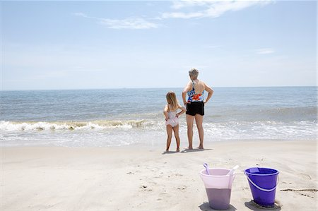 seniors woman in swimsuit - Senior woman with granddaughter with hands on hips looking out from beach Stock Photo - Premium Royalty-Free, Code: 614-08270213