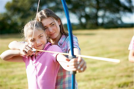 Girl learning archery from teenage sister Stock Photo - Premium Royalty-Free, Code: 614-08270381