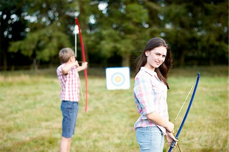 Portrait of teenage girl practicing archery with brother Stock Photo - Premium Royalty-Free, Code: 614-08270382