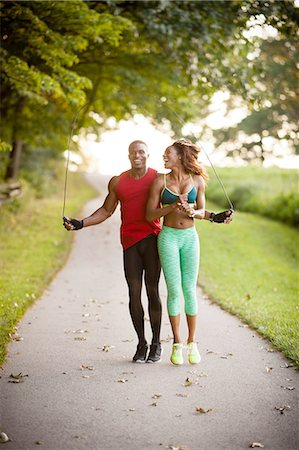 Young couple training on path skipping in unity Stock Photo - Premium Royalty-Free, Code: 614-08270508