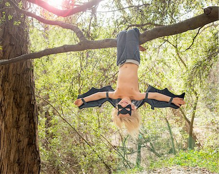 Young boy dressed as a bat, hanging from tree branch Stock Photo - Premium Royalty-Free, Code: 614-08307559