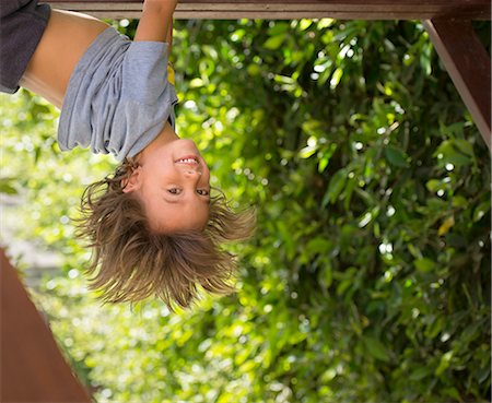 dangling - Young boy hanging upside-down Stock Photo - Premium Royalty-Free, Code: 614-08307583