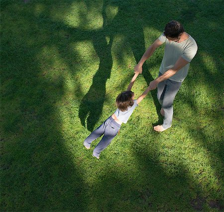 shadow - Father swinging son around, outdoors, elevated view Stock Photo - Premium Royalty-Free, Code: 614-08307592