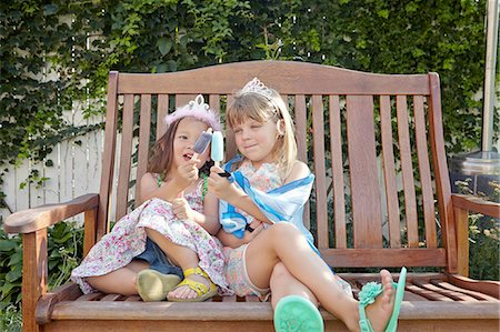 Girls enjoying ice lolly on garden bench Stock Photo - Premium Royalty-Free, Code: 614-08307639