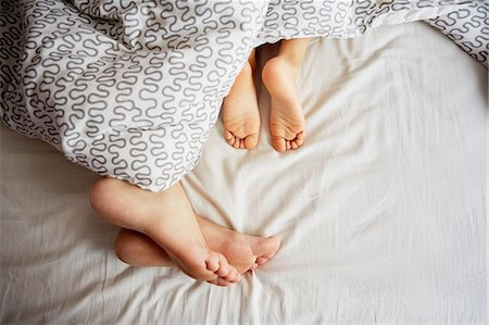 Bare feet of father and young son lying in bed Stock Photo - Premium Royalty-Free, Code: 614-08307737