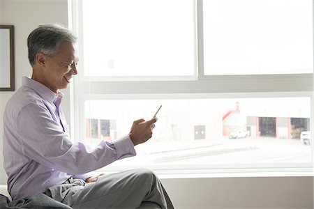 Side view of mature man sitting in front of window using smartphone Stock Photo - Premium Royalty-Free, Code: 614-08307892