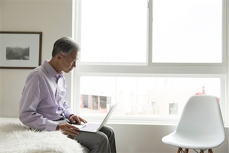 Side view of mature man sitting on edge of bed using laptop Stock Photo - Premium Royalty-Free, Code: 614-08307893