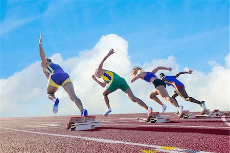 race track (people) - Four female athletes on athletics track, leaving starting blocks, rear view Stock Photo - Premium Royalty-Free, Code: 614-08307954