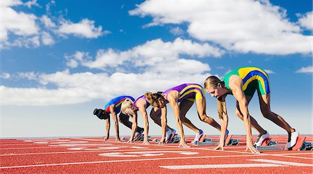 Four female athletes on starting blocks, about to start race Stock Photo - Premium Royalty-Free, Code: 614-08307951