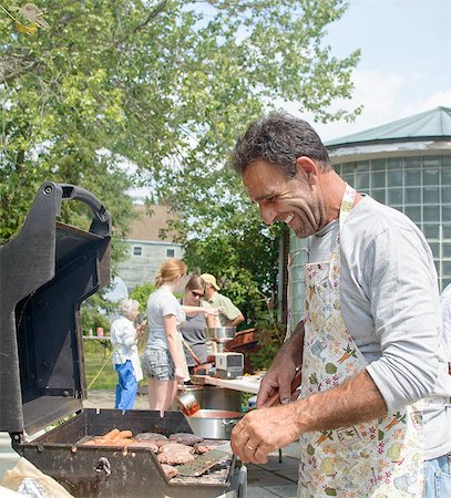 Side view of mature man cooking for family on barbecue looking down smiling Stock Photo - Premium Royalty-Free, Code: 614-08308018