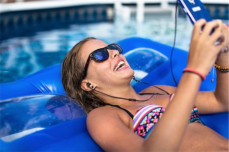Teenager using smartphone on inflatable in swimming pool Stock Photo - Premium Royalty-Free, Code: 614-08329176