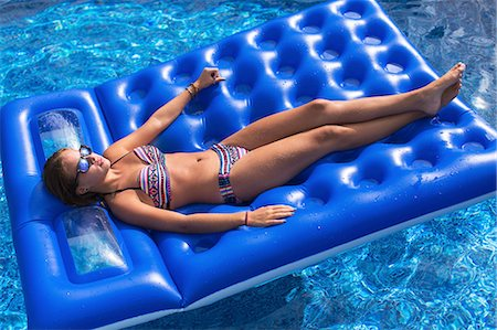Teenager relaxing on inflatable in swimming pool Stock Photo - Premium Royalty-Free, Code: 614-08329186