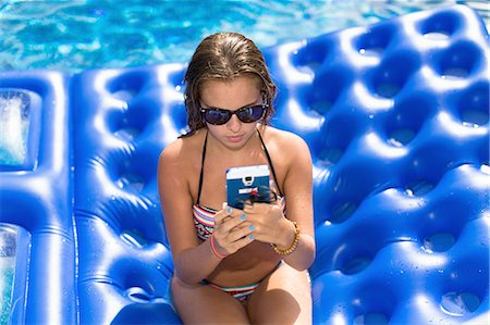 Teenager using smartphone on inflatable in swimming pool Stock Photo - Premium Royalty-Free, Code: 614-08329187
