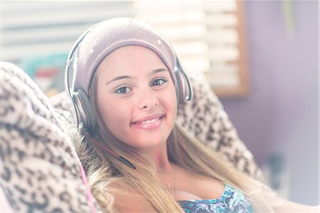 Teenager with earphones smiling on lazy chair Stock Photo - Premium Royalty-Free, Code: 614-08329182