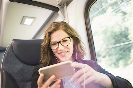 Mid adult woman on train, using smartphone, wearing earphones Stock Photo - Premium Royalty-Free, Code: 614-08329207