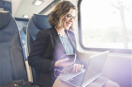 Mid adult woman on train, using smartphone and laptop Stock Photo - Premium Royalty-Free, Code: 614-08329210
