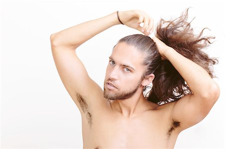 Young man with long hair, putting hair in ponytail Stock Photo - Premium Royalty-Free, Code: 614-08329389