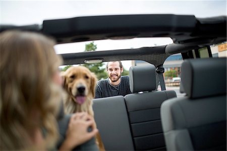 Young woman in jeep looking over her shoulder at dog and boyfriend Stock Photo - Premium Royalty-Free, Code: 614-08329405
