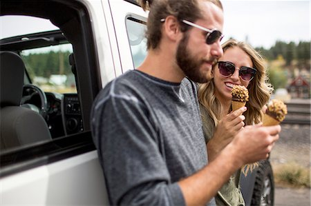 Young couple leaning against jeep eating ice cream cones Stock Photo - Premium Royalty-Free, Code: 614-08329409