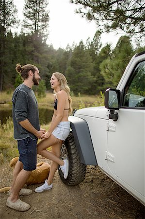 Young couple holding hands next to jeep on riverside, Lake Tahoe, Nevada, USA Stock Photo - Premium Royalty-Free, Code: 614-08329454